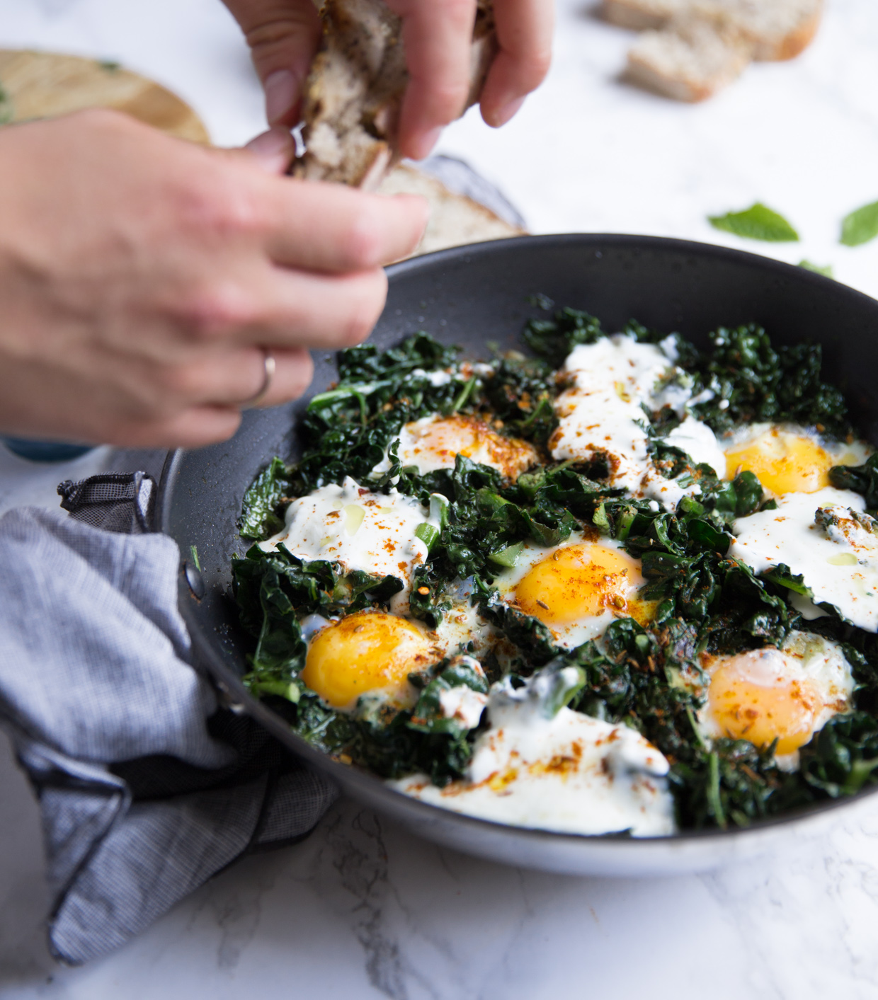 Green baked eggs with spicy yogurt